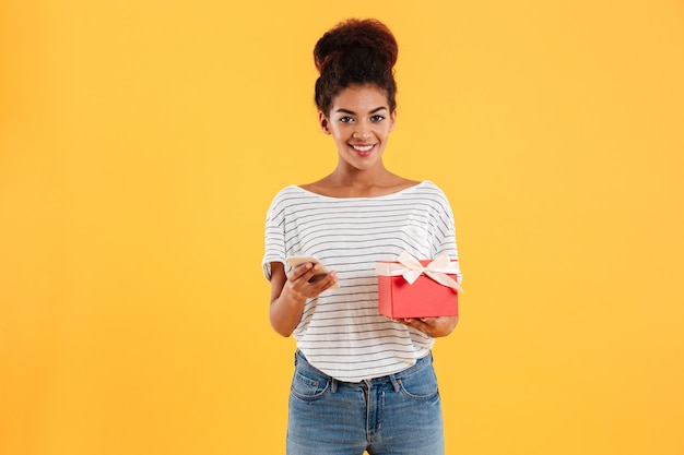 電話とプレゼントを保持している若い女性