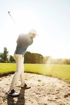 Мужской гольфист, ударяя мяч из песколовки