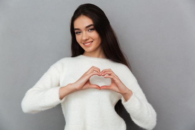 Молодая женщина подросток делает жест сердца руками