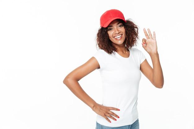 陽気なジェスチャーを示すキャップを身に着けている陽気な若いアフリカ女性。