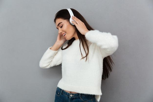 Счастливая женщина брюнет в свитере и наушниках слушая музыка
