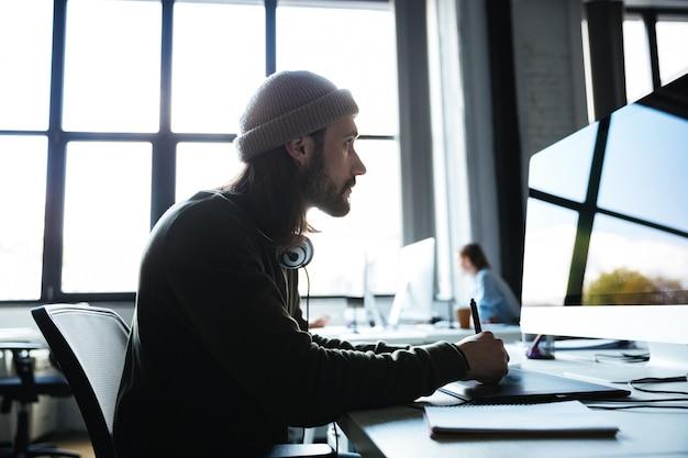 Человек работает в офисе, используя компьютер. глядя в сторону.