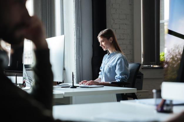 女性はコンピューターを使用してオフィスで働きます。よそ見。