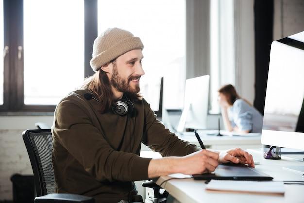 Красавец работа в офисе с помощью компьютера.
