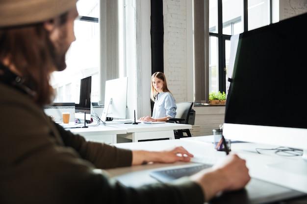 若い同僚はコンピューターを使用してオフィスで働く