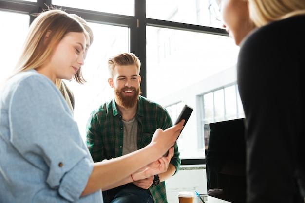 Молодые коллеги стоя в офисе используя планшет