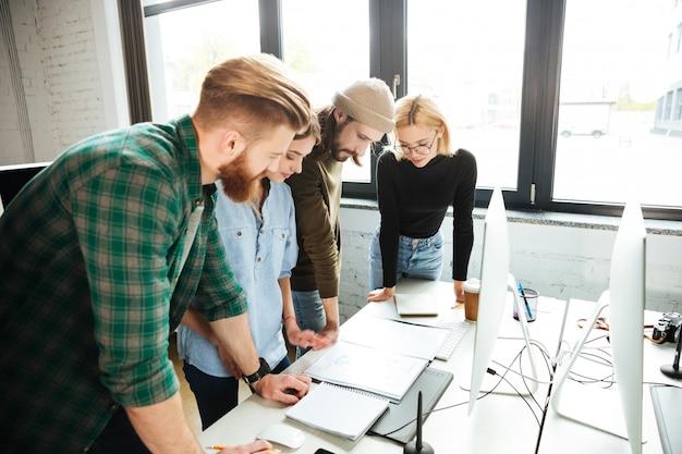 Сконцентрированные коллеги стоя в офисе