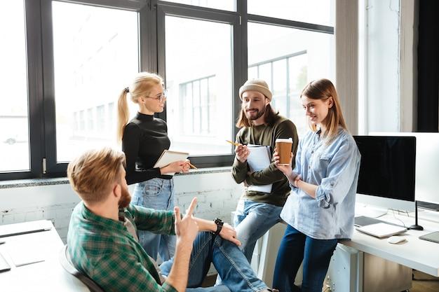Коллеги стоят в офисе и разговаривают друг с другом