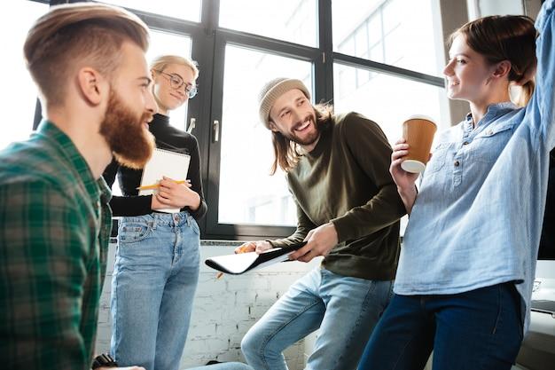 Концентрированные коллеги в офисе разговаривают друг с другом