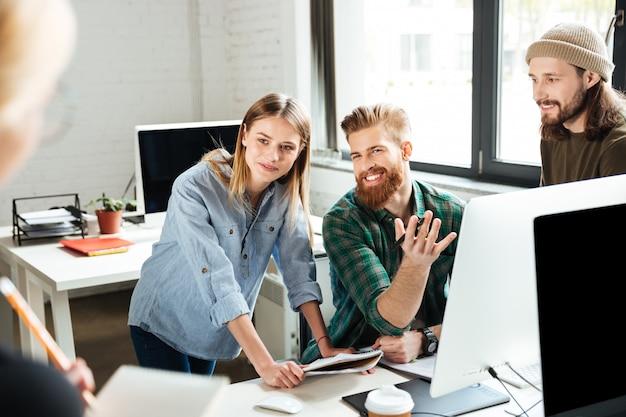 Счастливые коллеги в офисе разговаривают друг с другом