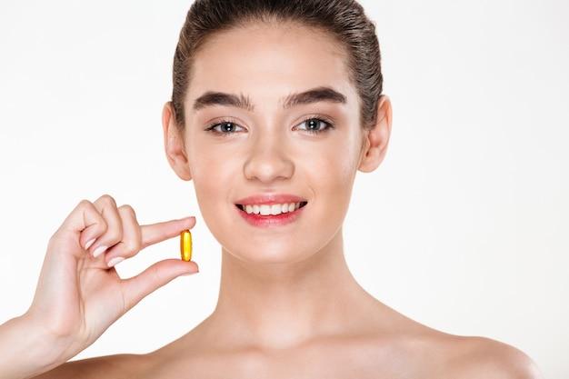 Портрет красоты усмехаясь здоровой женщины с темными волосами держа лекарства капсулы или витамин в ее представлять руки