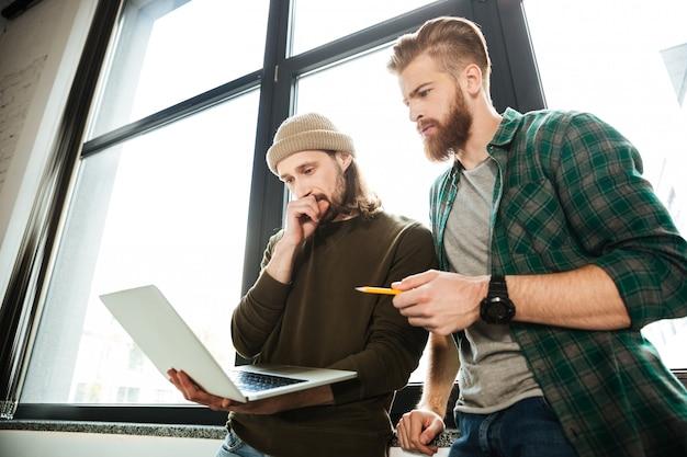Молодые концентрированные мужчины коллеги в офисе, используя ноутбук
