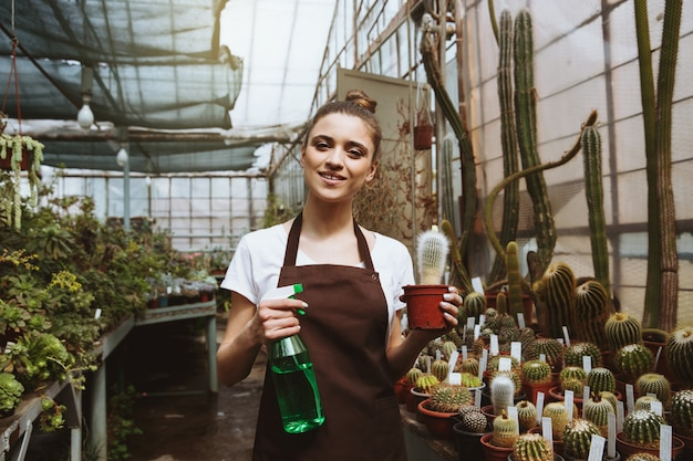 植物の近くの温室で立っている幸せな若い女