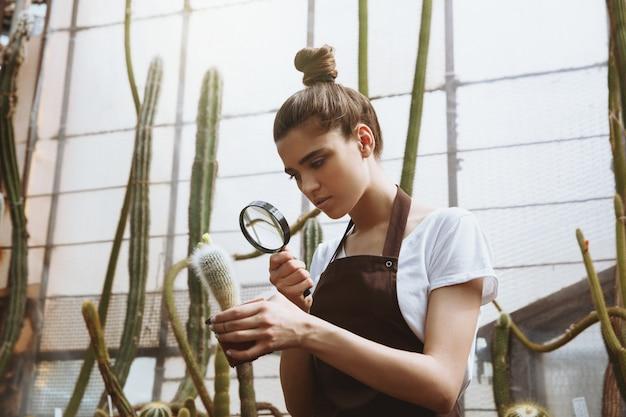 Серьезная молодая женщина, стоя в теплице возле растений
