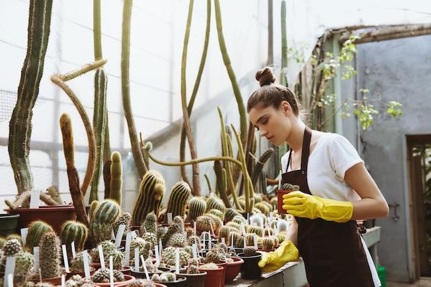 植物の近くの温室に立っている深刻な若い女性