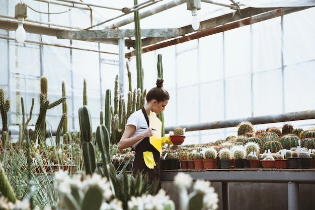 温室に立っている若い女性を集中