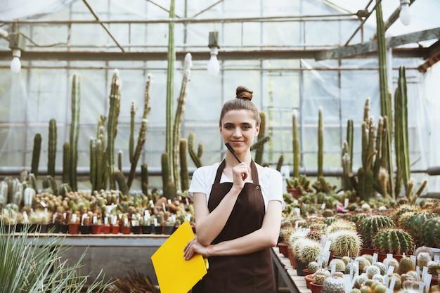 クリップボードを保持している温室に立っている幸せな若い女性