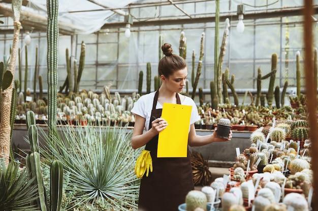 クリップボードを保持している温室に立っている深刻な若い女性