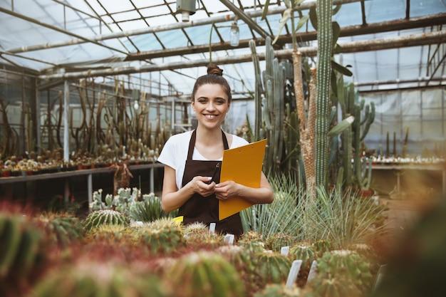 クリップボードを保持している温室に立っている幸せな若い女。