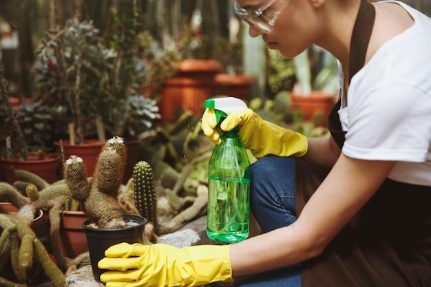 植物の近くの温室に立っているメガネの女性。