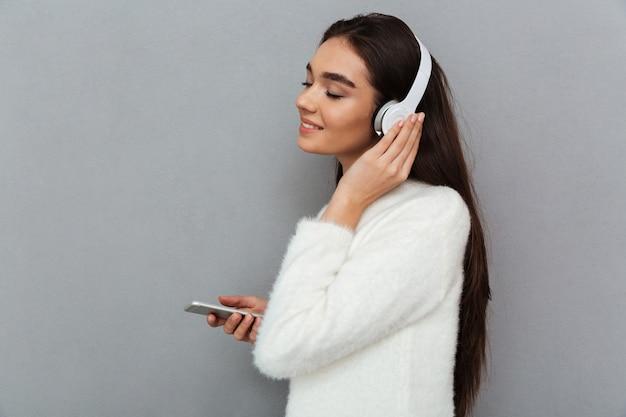 セーターとヘッドフォンで笑顔のブルネットの女性の側面図