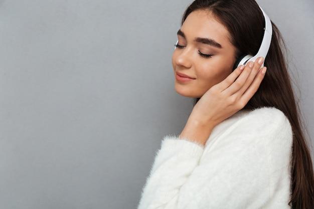 Взгляд со стороны счастливой женщины брюнет в свитере и наушниках