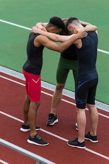Многонациональная команда спортсменов, стоя на беговой дорожке на открытом воздухе