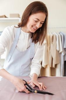 Женщина, используя ножницы, чтобы разрезать ткань