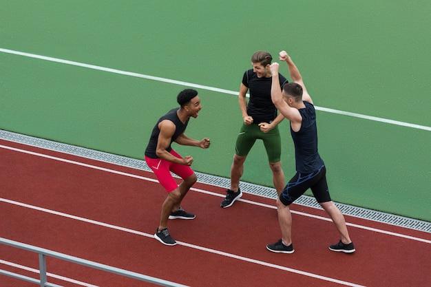 Счастливая многонациональная команда спортсменов делает жест победителя
