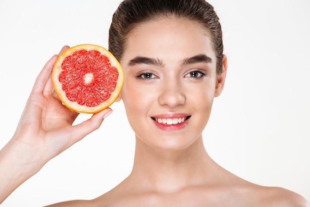 彼女の顔の近くのオレンジ色の柑橘類を押しながら見ている自然なメイクと半分裸の女性を笑顔のうれしそうな画像
