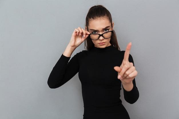 Портрет серьезной привлекательной женщины в черном платье