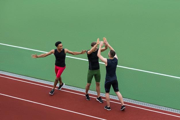 Многонациональная команда спортсменов, стоя на беговой дорожке