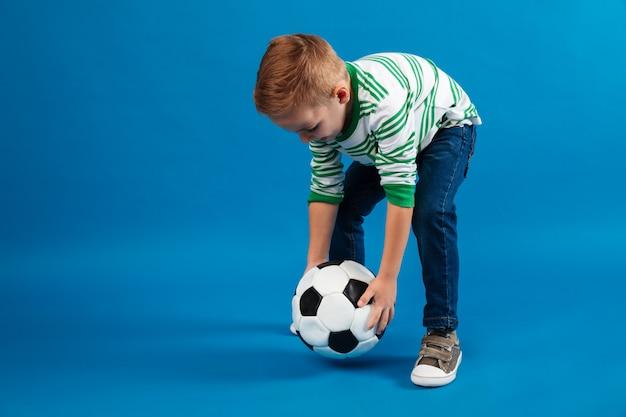 Портрет ребенка собирается пнуть футбольный мяч