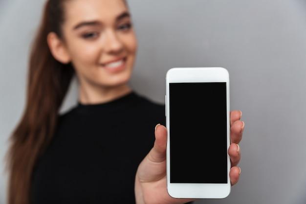 空白のスマートフォンの画面を示す黒い服を着て幸せなブルネットの女性