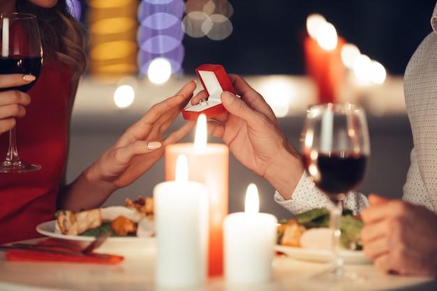 若い男が彼の女性に婚約指輪を与える