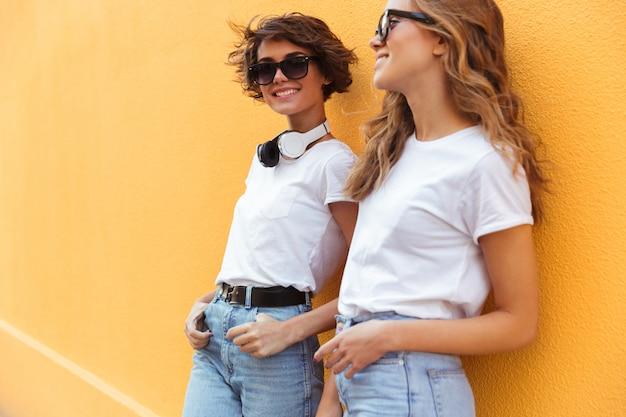 Две улыбающиеся молодые девушки позируют на улице