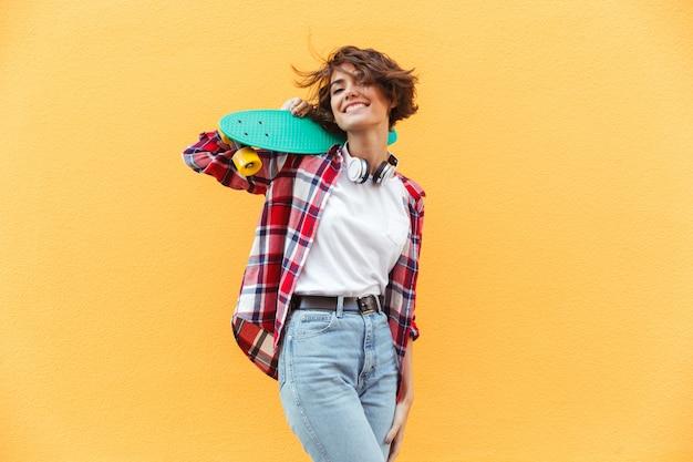 Веселая молодая девушка держит скейтборд на ее плечи