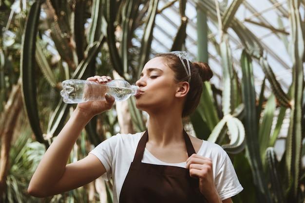 温室の飲料水に立っている深刻な若い女性。