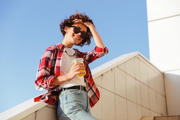 Беззаботная девушка в солнечных очках, пить апельсиновый сок