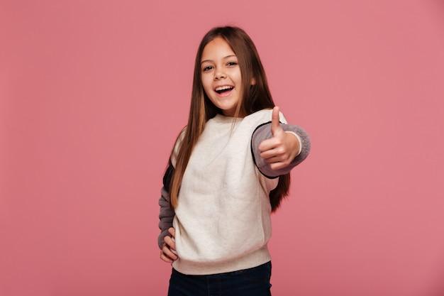 Счастливая девушка брюнетка показывает палец вверх и улыбается