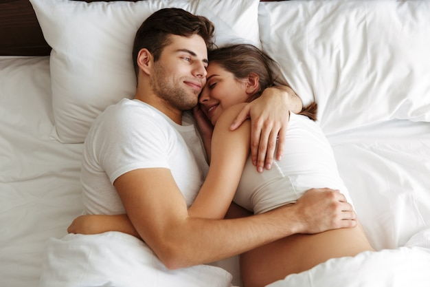 陽気な妊娠中の女性は夫とベッドにあります。