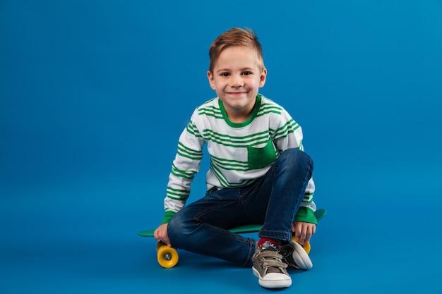 Улыбающийся молодой мальчик сидит на скейтборде и смотрит