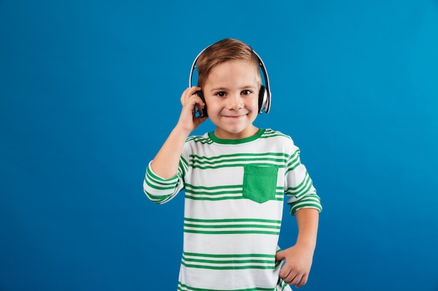 Улыбающийся молодой мальчик прослушивания музыки на наушники