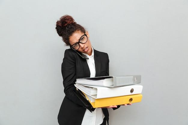 Молодая африканская бизнес-леди держа папки.