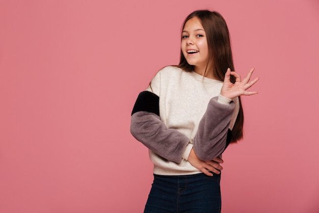 Улыбающаяся девушка в свитере смотрит и показывает жест