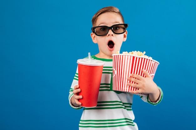 映画を見る準備をしている眼鏡のショックを受けた少年