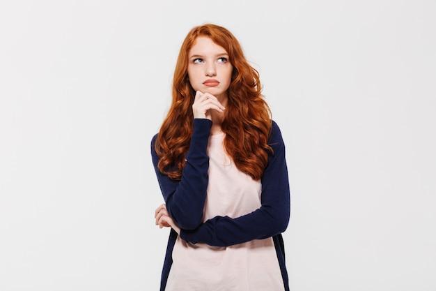 思慮深い若い赤毛の女性。よそ見。