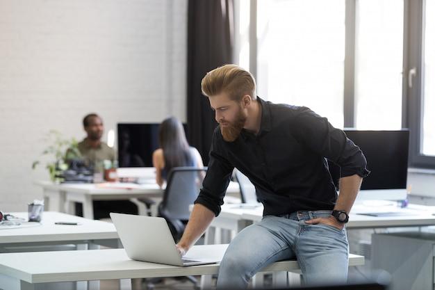 若い男が彼の机の上に座ってノートパソコンの画面を見て