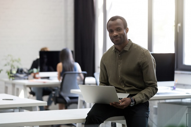 彼の机の上に座って笑顔幸せなアフロアメリカンビジネスマン