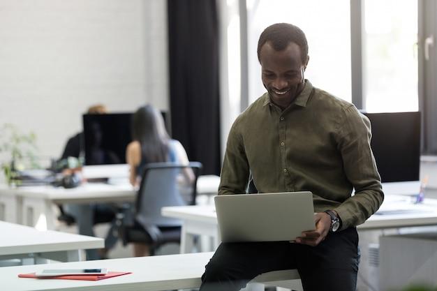 幸せなアフロアメリカンの実業家彼の机の上に座って、入力